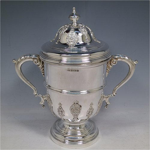 A Sterling Silver trophy cup and cover, in a George II style, having a round body with applied floral strap-work decoration, two scroll side-handles with anthemion leaf thumb-pieces, a central applied girdle band, a pull-off lid with matching applied strap-work and a cast round finial, and all sitting on a stepped pedestal foot. Made by J. A. Restall of Birmingham in 1926. The dimensions of this fine hand-made silver trophy cup and cover are height 26 cms (10.25 inches), spread across arms 24 cms (9.5 inches), and it weighs approx. 830g (27 troy ounces).