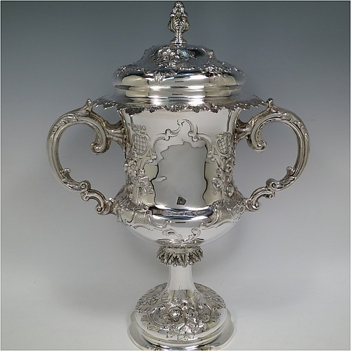 An Antique Victorian Sterling silver trophy cup and cover, in a Campana style, having a bellied body with vacant cartouches on both sides, and hand-chased floral and scroll-work decoration, with two cast anthemion leaf scroll handles, the original domed lid with matching decoration and a cast foliate finial, all sitting on a spreading pedestal foot. Made by Thomas Smiley of London in 1864. The dimensions of this fine hand-made antique silver trophy cup and cover are height 36.5 cms (14.3 inches), spread across handles 29 cms (11.5 inches), and it weighs approx. 1,150g (37 troy ounces).