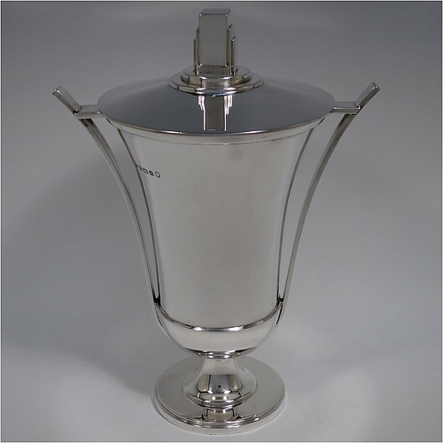 A Sterling Silver Art Deco trophy cup and cover, having a very plain round body with tapering sides, two geometrically styled side-handles, a lift-off lid with cast stepped rectangular finial, and sitting on a pedestal foot. Made by the Adie Brothers of Birmingham in 1934. The dimensions of this fine hand-made silver Art Deco trophy cup are height 24 cms (9.5 inches), spread across arms 18 cms (7 inches), and it weighs approx. 743g (24 troy ounces).