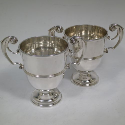 A very handsome Antique Edwardian Sterling Silver pair of trophy cups in a George II style, having plain round bodies with applied reeded borders, two flying scroll side-handles, central applied girdle bands, and all sitting on stepped pedestal feet. Made by Skinner and Co., of Sheffield in 1908. The dimensions of these fine hand-made antique silver trophy cups are height 14.5 cms (5.75 inches), spread across arms 17 cms (7.75 inches), and they weigh a total of approx. 624g (20 troy ounces).