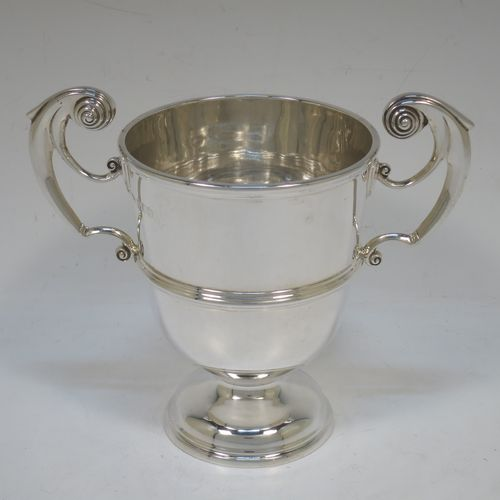 A very handsome Antique Edwardian Sterling Silver trophy cup in a George II style, having a plain round body with applied reeded borders, two flying scroll side-handles, a central applied girdle band, and all sitting on a stepped pedestal foot. Made by Skinner and Co., of Sheffield in 1908. The dimensions of this fine hand-made antique silver trophy cup are height 14.5 cms (5.75 inches), spread across arms 17 cms (7.75 inches), and it weighs approx. 312g (10 troy ounces).