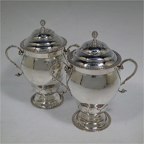 A very unusual pair of Sterling Silver trophy cups and covers, in an Arts and Crafts style, having round bellied bodies with hand-hammered decoration, applied zigzag borders and cut-card work, two side scroll handles with beaded thumb-pieces, removable covers with spiral finials, and all sitting on stepped pedestal feet. Made by D. and J. Wellby of London in 1931. The dimensions of these fine hand-made silver trophy cups and covers are height 17.5 cms (7 inches), spread across arms 15 cms (6 inches), and they weigh a total of  approx. 825g (26.6 troy ounces).