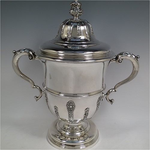 A very handsome Antique Edwardian Sterling Silver trophy cup and cover, in a George II style, having a round body with applied floral strap-work decoration, two scroll side-handles with anthemion leaf thumb-pieces, a central applied girdle band, a pull-off lid with matching applied strap-work and a cast round floral finial, and all sitting on a stepped pedestal foot. Made by Walker and Hall of Sheffield in 1909. The dimensions of this fine hand-made antique silver trophy cup and cover are height 37 cms (14.5 inches), spread across arms 33 cms (13 inches), and it weighs approx. 1,570g (51 troy ounces).