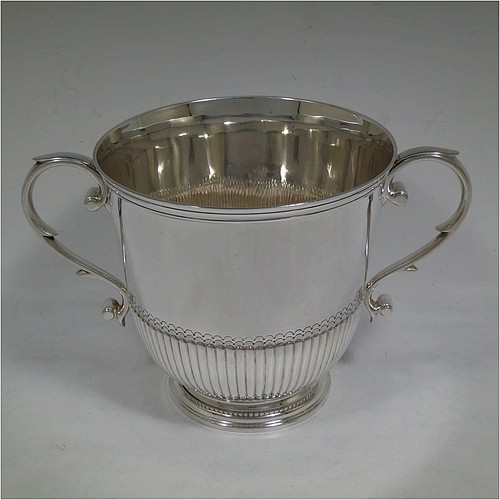 A very handsome Sterling Silver trophy cup in a George III neoclassical style, having a round body with tapering sides and half-fluted decoration, with hand-chased reeded borders, two cast scroll side-handles, and all sitting on a pedestal foot. Made by Charles and Richard Comyns of London in 1921. The dimensions of this fine hand-made silver trophy cup are height 14.5 cms (5.75 inches), spread across arms 24 cms (9.5 inches), and it weighs approx. 683g (22 troy ounces).