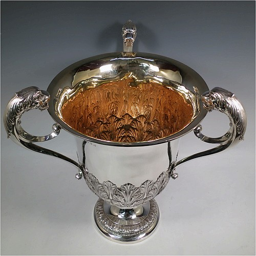A very large, heavy, and handsome Antique Edwardian Sterling Silver three-handled trophy cup, having a round body with tapering sides and hand-chased half anthemion leaf decoration, with a  gold-gilt interior, three cast flying scroll handles with leopard face terminals, and all sitting on a pedestal foot. Made by Goldsmiths and Silversmiths of London in 1905. The dimensions of this fine hand-made large antique silver trophy cup are height 43 cms (17 inches), spread across arms 38 cms (15 inches), and it weighs approx. 3,225g (104 troy ounces).