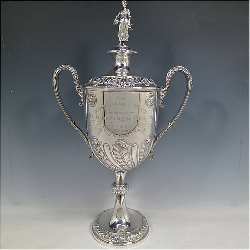 An Antique Victorian large Sterling Silver trophy cup and cover, having a round hand-chased body with fluted, floral, and anthemion leaf decoration, two cast side-handles with anthemion leaf thumb-pieces, an original cover with cast Milk-Maid finial, and sitting on a pedestal foot. Made by Horace Woodward & Co.Ltd, of London in 1899. The dimensions of this fine hand-made antique silver trophy cup & cover are height 51 cms (20 inches), spread across arms 30 cms (11.75 inches), and it weighs approx. 1,635g (53 troy ounces). Please note that this has engraved full armorial crest on one side and a presentation inscription on the other side of the body.