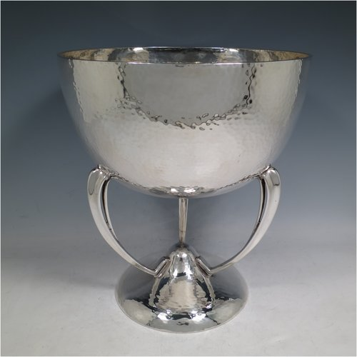 An Antique Edwardian sterling silver Art Nouveau style trophy cup, having a round body with hand-hammered decoration, sitting on three supports that are attached to a spreading pedestal foot. Made by Goldsmiths & Silversmiths of London in 1906. The dimensions of this fine hand-made antique silver trophy cup are height 28 cms (11 inches), diameter at lip 25.5 cms (10 inches), and it weighs approx. 1,763g (56.9 troy ounces).