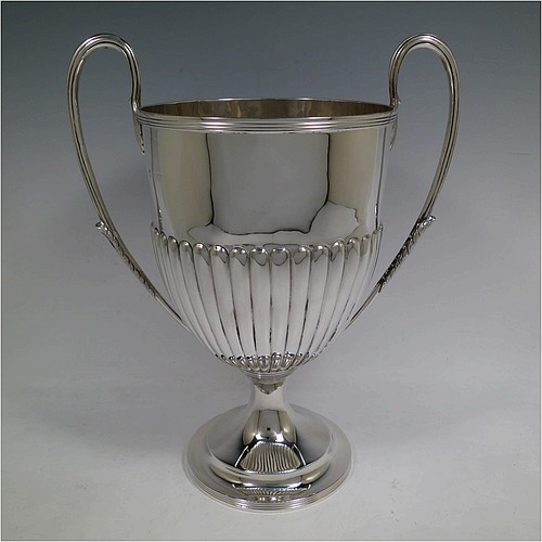 A very handsome Antique Victorian Sterling Silver trophy cup in a George III neoclassical style, having a round body with tapering sides and half-fluted decoration, with hand-chased reeded borders, two looped side-handles with anthemion leaves, and all sitting on a pedestal foot. Made by Charles Stuart Harris of London in 1895. The dimensions of this fine hand-made antique silver trophy cup are height 32.5 cms (12.75 inches), spread across arms 26.5 cms (10.5 inches), and it weighs approx. 940g (30 troy ounces).
