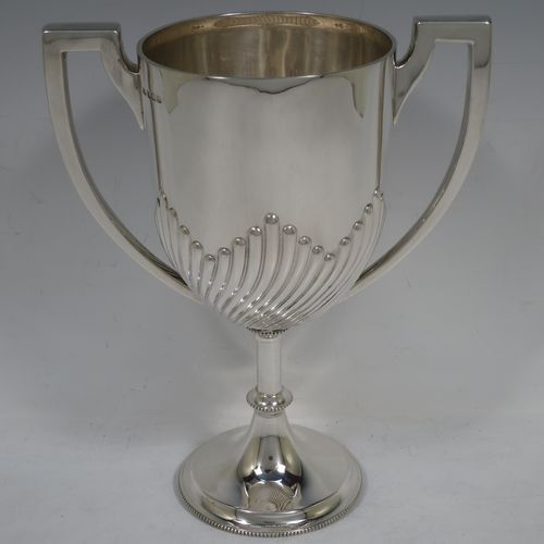 A handsome Antique Edwardian Sterling Silver trophy cup in a George III neoclassical style, having a round body with tapering sides and half-fluted decoration, two plain flat-topped side-handles, and all sitting on a pedestal foot with bead-edged borders. Made by Mappin and Webb of London in 1904. The dimensions of this fine hand-made antique silver trophy cup are height 23 cms (9 inches), spread across arms 18 cms (7 inches), and it weighs approx. 558g (18 troy ounces).