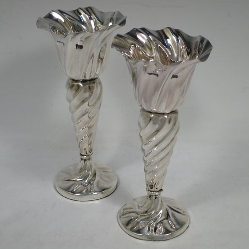 A very pretty Art Nouveau Antique Edwardian Sterling Silver pair of vases, having round bodies with tapering sides all hand-chased with swirl-fluted decoration, and all sitting on round pedestal bases. Made by Walker and Hall of Birmingham in 1902. The dimensions of this fine pair of hand-made antique silver vases are height 17 cms (6.75 inches), and diameter at rims 8 cms (3 inches).