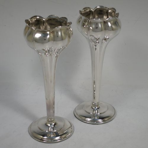 A very pretty Art Nouveau Antique Edwardian Sterling Silver pair of vases, having round bodies with tapering sides all hand-chased to represent a budding tulip with fluted decoration, and all sitting on round pedestal stepped bases. Made by Jones and Crompton of Birmingham in 1906. The dimensions of this fine pair of hand-made antique silver vases are height 16 cms (6.3 inches), and diameter at rims 6 cms (2.3 inches).