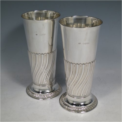 An Antique Victorian Sterling silver pair of table flower vases, having round bodies with tapering sides, hand-chased half-fluted decoration, and sitting on pedestal feet. Made by Henry Stratford of London in 1889. The dimensions of these fine hand-made antique silver pair of vases are height 19 cms (7.5 inches), diameter at top 8.5 cms (3.3 inches), and they weigh a total of approx. 487g (15.7 troy ounces). Please note that these vases are not loaded.