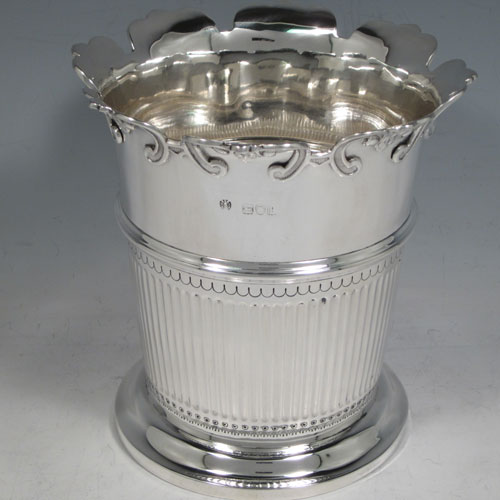 Antique Victorian sterling silver single fern pot vase, having a round body with tapering sides, with hand-chased half-fluted decoration,  a central vacant cartouche, an applied shaped and scrolled border, and sitting on a pedestal foot. Made by the Barnard Brothers of London in 1901. The dimensions of this fine hand-made silver vase are height 15 cms (6 inches), diameter at top 15 cms (6 inches), and it weighs approx. 452g (14.6 troy ounces). Please note that this vase is not loaded.
