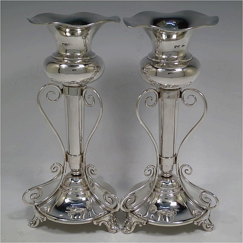 A very pretty and unusual pair of Antique Edwardian Sterling Silver Art Nouveau style vases, having removable central bodies, sitting in a frame with wire-work scrolls, attached to round bases with three scroll feet. Made by Walker and Hall of Sheffield in 1907. The dimensions of this fine pair of hand-made antique silver Art Nouveau vases are height 24 cms (9.5 inches), and diameter at bases 11 cms (4.3 inches). Please note that these vases are not loaded, and the total weight of silver is 640g (20.6 troy ounces)..