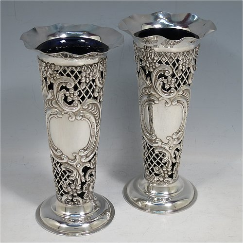 An Antique Victorian Sterling Silver pair of vases, having hand-chased and pierced bodies with floral decoration on round tapering sides, with vacant cartouches on one side, removable blue-glass liners, with wavy-edge rims and and sitting on pedestal feet. Made by the William Comyns of London in 1897. The dimensions of this fine hand-made pair of antique silver vases are height 18 cms (7 inches), diameter at top 9 cms (3.5 inches), and they weigh a total of 272g (8.8 troy ounces).