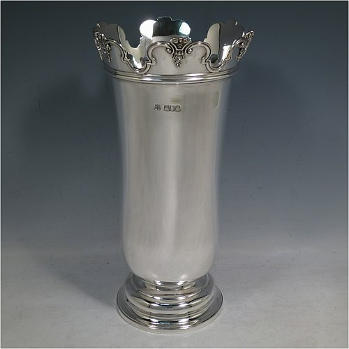 An Antique Victorian Sterling Silver large table flower vase, having a plain round body with straight sides and a tucked under belly, with an applied scroll top border, and sitting on a stepped pedestal foot. Made by D. & J. Welby of London in 1898. The dimensions of this fine hand-made antique silver vase are height 26 cms (10.25 inches), diameter at top 13.5 cms (5.3 inches), and it weighs approx. 703g (22.6 troy ounces). Please note that this vase is not loaded.