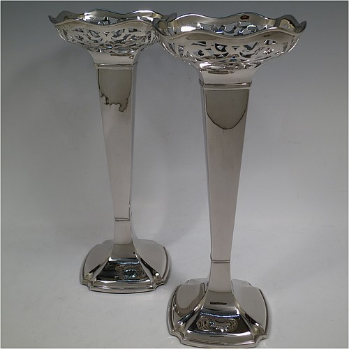 A very handsome and large pair of Antique Sterling Silver table flower vases, having plain square cross-section panelled bodies with tapering sides, with hand-pierced floral and scroll style decoration at the top, and sitting on pedestal feet with cut corners. Made by Charles Cheshire of Chester in 1918. The dimensions of these fine hand-made antique silver pair of vases are height 28 cms (11 inches), and width at top 13 cms (5 inches).
