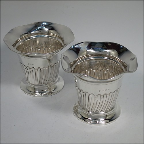 An Antique Edwardian Sterling silver pair of table flower or fern pot vases, having round bodies with wavey-edge borders and tapering sides, hand-chased half-fluted decoration, and sitting on pedestal bases. Made by William Hutton and Sons of Birmingham in 1907. The dimensions of these fine hand-made antique silver pair of vases are height 8 cms (3.25 inches), diameter at top 10 cms (4 inches), and they weigh a total of approx. 155g (5 troy ounces). Please note that these vases are not loaded.
