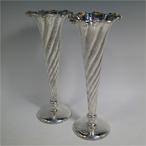 An Antique Edwardian Sterling Silver pair of Art Nouveau vases, having hand-hammered round bodies with tapering sides, and hand-chased swirl fluting, sitting on plain round pedestal bases. Made by Stokes and Ireland, one from London in 1904, and the other from Chester in 1902. The dimensions of this fine pair of hand-made antique silver Art Nouveau vases are height 14.5 cms (5.75 inches), and diameter at bases 25.5 cms (10 inches). Please note that these vases are loaded in the bases.