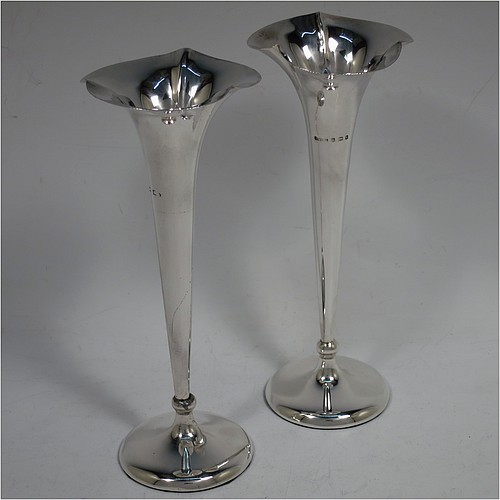 A pretty Antique Edwardian Sterling Silver pair of table flower vases, having plain round tapering bodies, with fluted mouths, and sitting on matching pedestal feet. Made by Saunders and Shepherd of Birmingham in 1903. The dimensions of these fine hand-made pair of antique silver vases are height 17 cms (6.75 inches), and diameter at top 6.5 cms (2.5 inches).