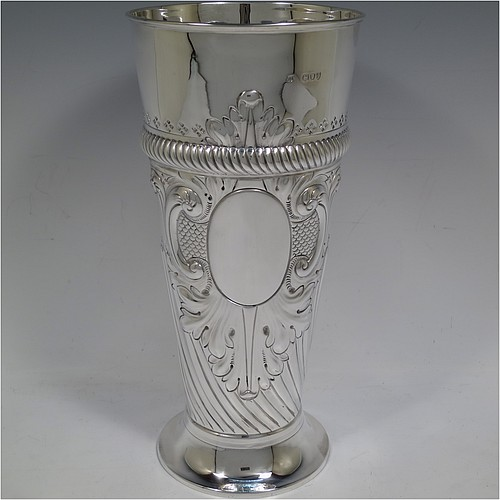 A very handsome Antique Victorian Sterling Silver large table flower vase, having a tapering round body, with hand-chased swirl fluted decoration, an oval vacant cartouche surrounded by hand-chased anthemion leaves and scrolls, with an upper band of gadroon rope-twist work, and sitting on a pedestal foot. Made by Thomas Bradbury of London in 1894. The dimensions of this fine hand-made antique silver vase are height 27.5 cms (10.75 inches), diameter at top 13 cms (5 inches), and it weighs approx. 433g (14 troy ounces). Please note that this vase is not loaded.
