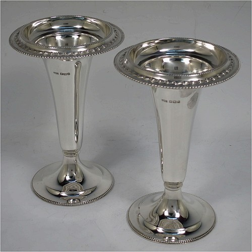 A very pretty pair of Antique Sterling Silver table flower vases, having plain round bodies with tapering sides, with applied bead and floral top borders, and sitting on plain round pedestal feet with matching bead-work. Made by James Dixon and Sons of Sheffield in 1913. The dimensions of these fine hand-made antique silver pair of vases are height 13 cms (5 inches), diameter at top 8.5 cms (3.3 inches), and they weigh a total of approx. 185g (6 troy ounces). Please note that these vases are not loaded.