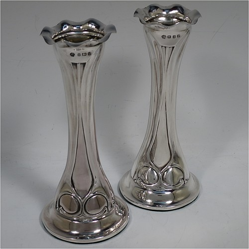 A very pretty Antique Victorian Sterling Silver pair of Art Nouveau table flower vases, having round bodies with tapering sides and hand-chased Art Nouveau style floral decoration, with wavy-edged rims, and all sitting on flat round pedestal feet. Made by William Hutton of Birmingham in 1901. The dimensions of these fine hand-made antique silver pair of vases are height 16 cms (6.5 inches), and diameter at base 7 cms (2.75 inches).