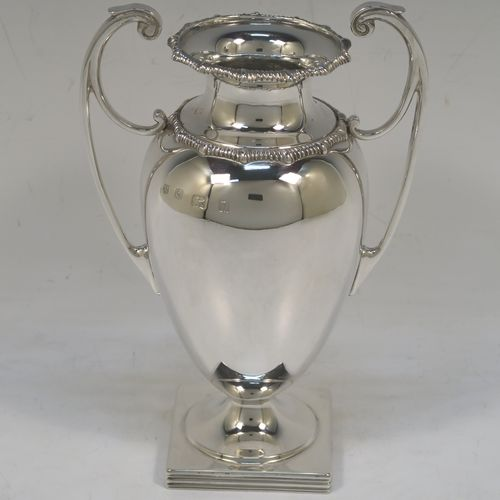 A heavy and very handsome Antique Sterling Silver single vase, having a plain round body with tapering sides, with two flying scroll side handles, with applied shaped gadroon top borders, and all sitting on a pedestal foot with a square base. Made by Stewart Dawson and Co., of Birmingham in 1912. The dimensions of this fine hand-made antique silver vase are height 17 cms (6.5 inches), spread across arms 12 cms (4.75 inches), diameter of body at widest point 8 cms (3 inches), and it weighs approx. 311g (10 troy ounces). Please note that this vase is not loaded.