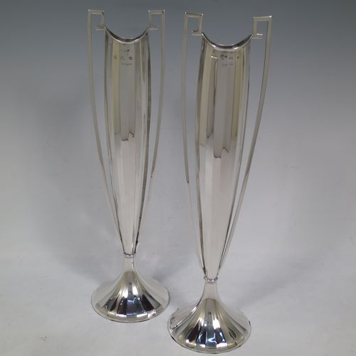 A very unusual and pretty pair of Art Deco Sterling Silver table flower vases, having tall panelled bodies with square cross-section side handles, and sitting on pedestal feet. Made by William Henry Sparrow of Birmingham in 1938. The dimensions of these fine hand-made pair of Art Deco silver vases are height 30 cms (11.75 inches), and diameter at base 8 cms (3.25 inches).