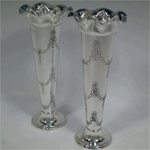 A very handsome antique Edwardian Sterling Silver pair of table flower vases, having round bodies with tapering sides and hand-chased floral swag decoration, with wavey-edge top borders, and sitting on round pedestal feet. Made by Samuel Walton Smith of Birmingham in 1902. The dimensions of these fine hand-made antique silver pair of vases are height 20 cms (8 inches), diameter at top 9 cms (3.5 inches), and they weigh a total of 310g (31 troy ounces). Please note that these vases are not loaded.