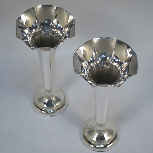 A pretty pair of Antique Sterling Silver table flower vases, having plain panelled tapering bodies, with fluted mouths and small bead borders, and sitting on plain round pedestal feet. Made by William Hutton of London in 1911. The dimensions of these fine hand-made pair of antique silver vases are height 18 cms (7 inches), and diameter at top 8 cms (3.25 inches).