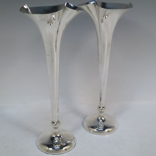A tall and handsome Antique Edwardian Sterling Silver pair of table flower vases, having plain round tapering bodies, with fluted mouths, and sitting on matching pedestal feet. Made by Asprey of Birmingham in 1903. The dimensions of these fine hand-made pair of antique silver vases are height 26 cms (10.25 inches), and diameter at top 10 cms (4 inches).