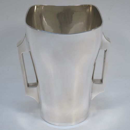 A very stylish Arts and Crafts Antique Edwardian Irish Sterling Silver table flower vase, having a square body with rounded corners and tapering sides, with two geometrical style side-handles, and all sitting on a flat base. Made Edmund Johnson of Dublin in 1903. The dimensions of this fine hand-made antique Irish silver vase are height 14 cms (5.5 inches), width across corners at top 11 cms (4.3 inches), and it weighs approx. 305g (9.8 troy ounces). Please note that this vase is not loaded.