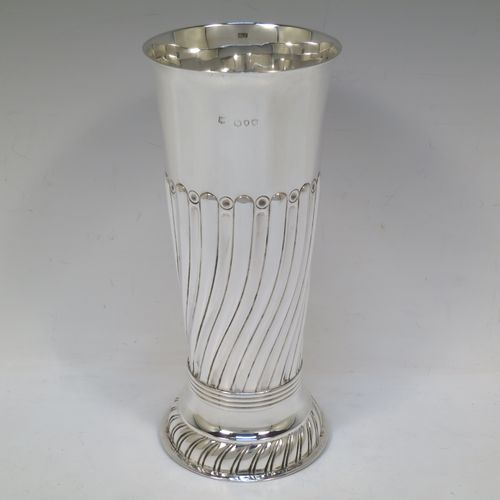 A handsome Antique Victorian Sterling Silver large table flower vase, having a round body with straight tapering sides, with hand-chased half swirl-fluted decoration, and sitting on a fluted pedestal foot. Made by Gibson and Langland of London in 1890. The dimensions of this fine hand-made antique silver vase are height 22 cms (8.75 inches), diameter at top 9.5 cms (3.75 inches), and it weighs approx. 286g (9.2 troy ounces). Please note that this vase is not loaded.