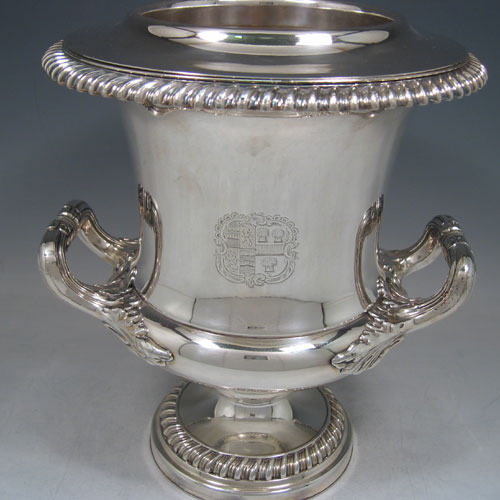 A very hansome pair of Antique Georgian Old Sheffield silver-plated wine coolers in the Campana style, with applied garoon borders, two side-handles with anthemion leaf mounts, with original interiors and covers, and all sitting on pedestal feet. Made in ca. 1815. The dimensions of this fine pair of hand-made antique Old Sheffield silver plated wine coolers are height 27 cms (10.5 inches), width across handles 24 cms (9.5 inches). Please note that these items are crested.