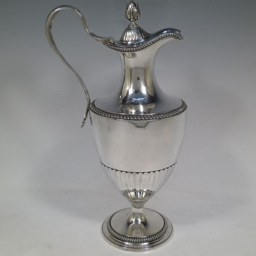 A very handsome and rare Antique Georgian Sterling Silver wine ewer, having an amphora style round bellied body, with applied gadroon borders and hand-chased half-fluted decoration, a hinged lid with cast anthemion leaf finial and a classical scroll handle, and all sitting on a pedestal foot. Made by Daniel Smith and Robert Sharp of London in 1784. The dimensions of this fine hand-made antique silver wine ewer are height 31 cms (12.25 inches), length 17 cms (6.75 inches), and it weighs approx. 840g (27 troy ounces).