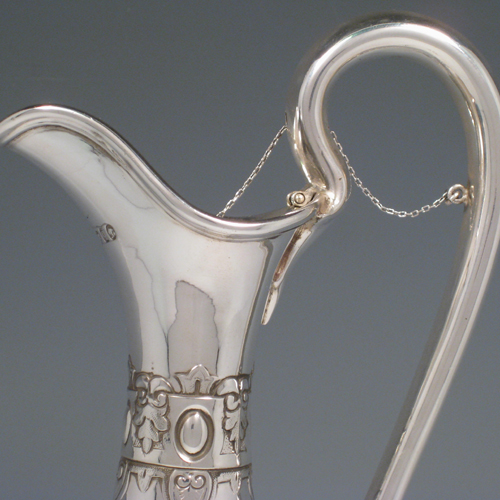 Antique Victorian sterling silver hand-chased wine ewer with unusual opening chain mechanism, with floral swags and cast ladies faces. Made by the Barnard Brothers of London in 1871. Height 35 cms (13.75