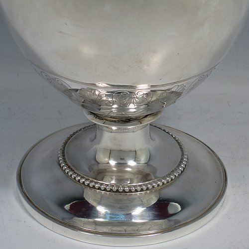 An Antique Victorian Sterling Silver wine ewer, having an amphora style round bellied body, with a band of hand-engraved floral decoration, together with applied bead borders, a lid with flat invisible hinge, a scroll handle with thumb-piece, and all sitting on a pedestal foot. Made by Arthur Sibley of London in 1869. The dimensions of this fine hand-made antique silver wine ewer are height 34 cms (13.3 inches), length 16 cms (6.25 inches), and it weighs approx. 848g (27 troy ounces).