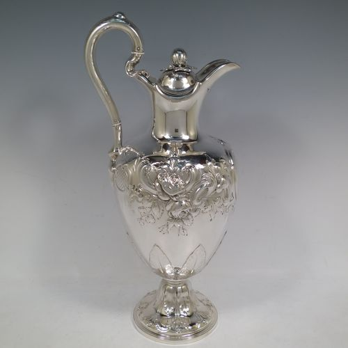 A beautiful Antique Victorian Sterling Silver wine ewer, having an amphora style round bellied body, with hand-chased floral and scroll decoration, a hinged lid with cast finial, an insulated scroll handle, and all sitting on a pedestal foot. Made by the Barnard Brothers of London in 1849. The dimensions of this fine hand-made antique silver wine ewer are height 35 cms (13.5 inches), length 16.5 cms (6.5 inches), and it weighs approx. 868g (28 troy ounces).